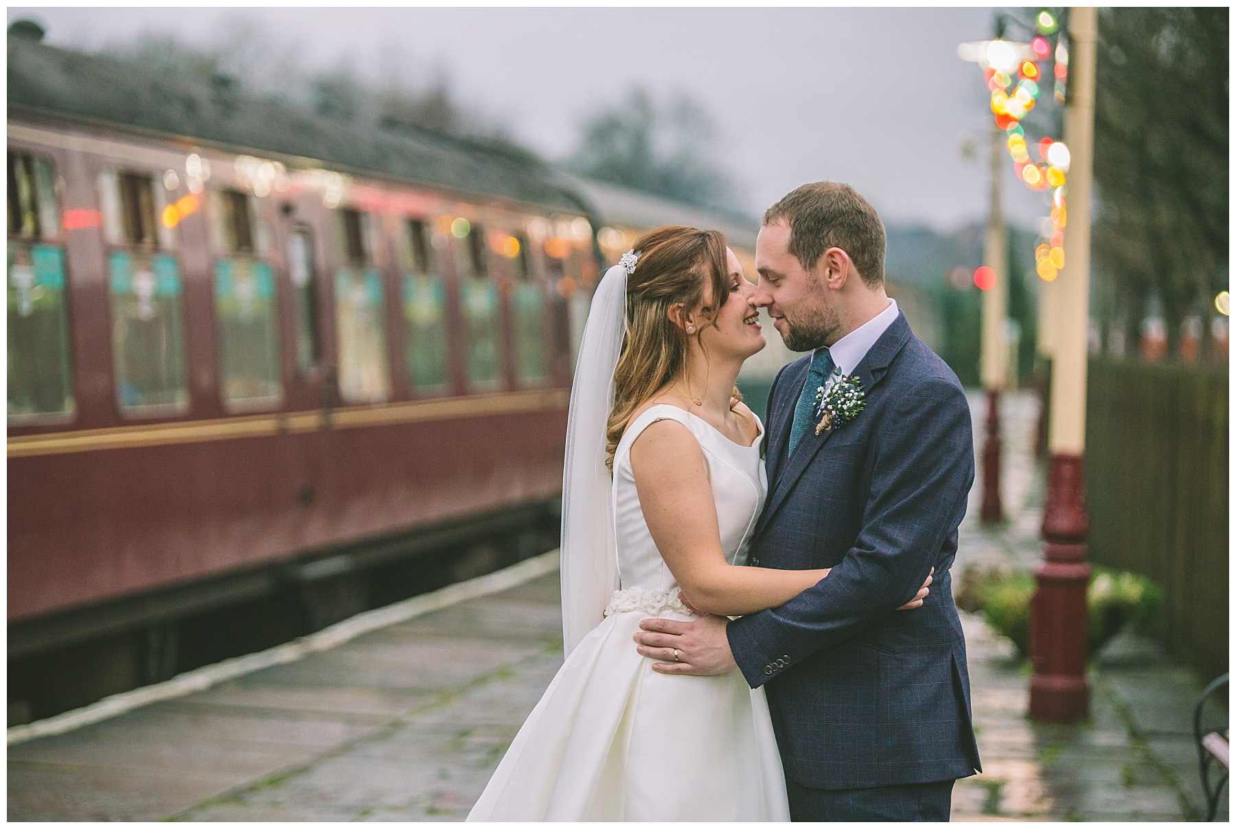 Wedding couple stand on steam rail platform