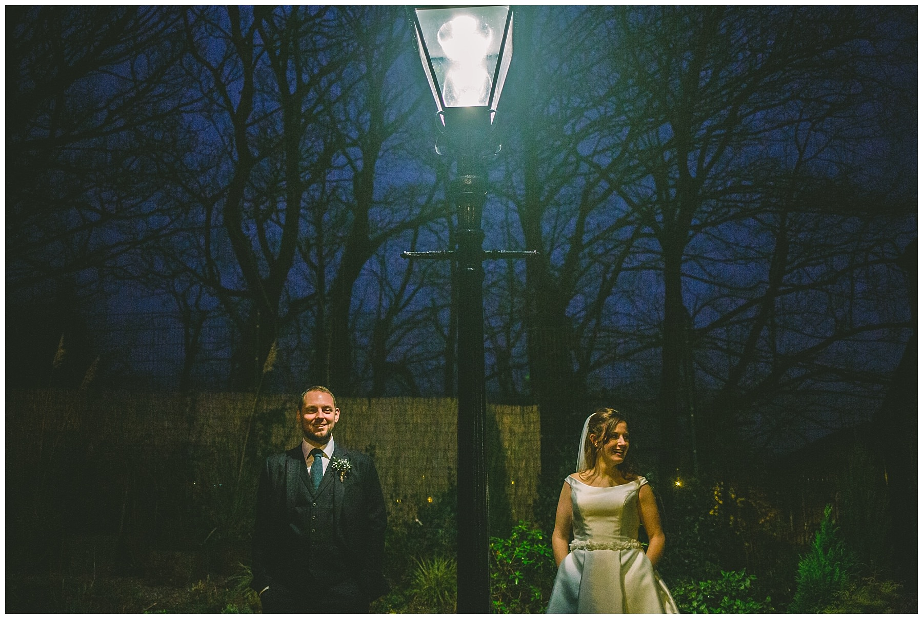 Couple stand cool under victorian street lamp for wedding portraits