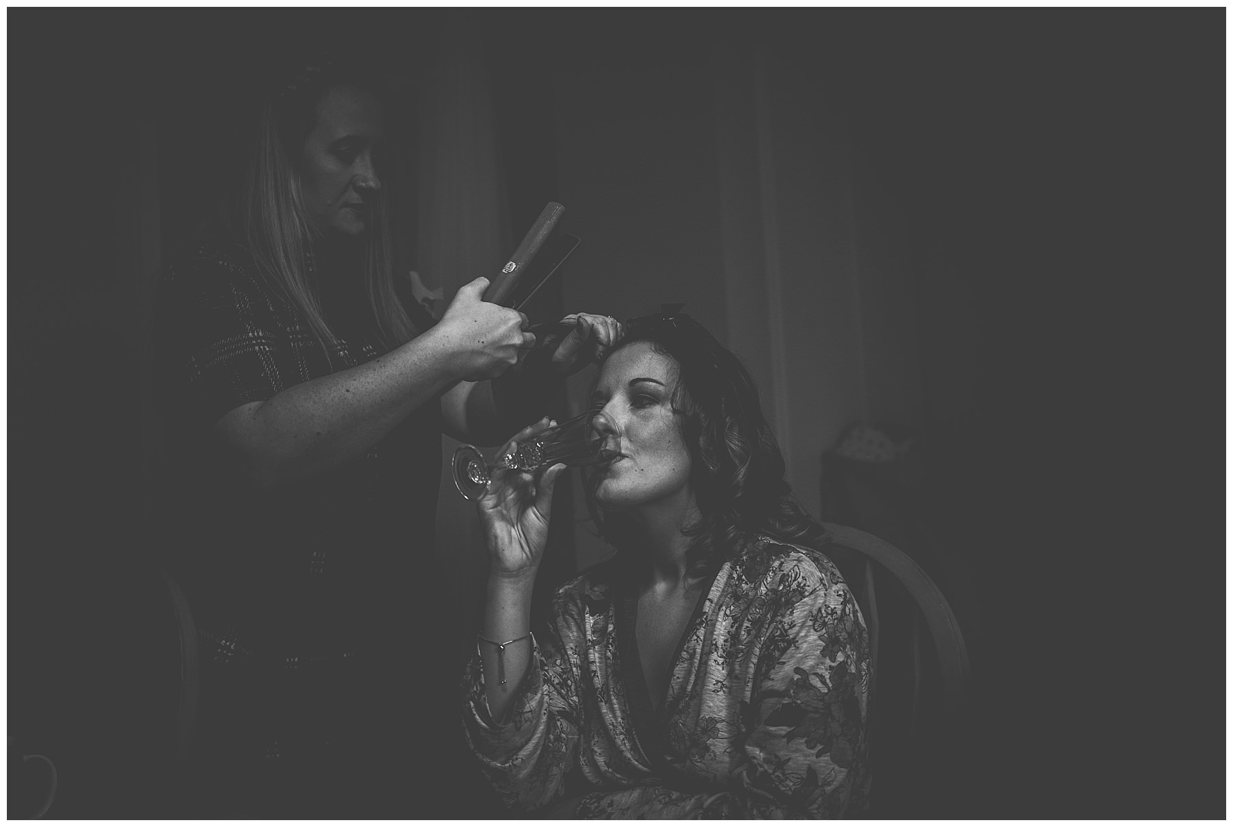Black and white shot of bride having her hair done for her wedding