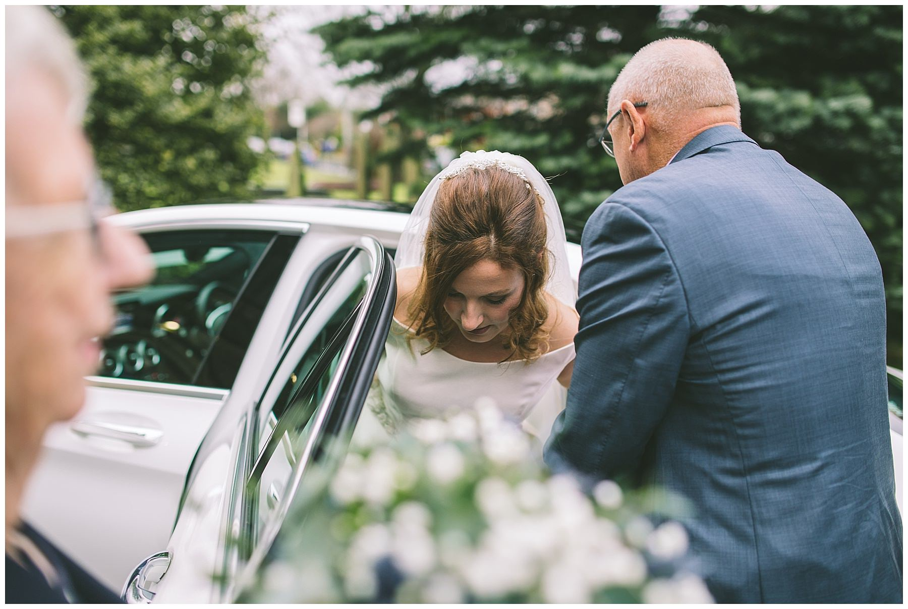 Brides dad helps her out of car as she arrives at church