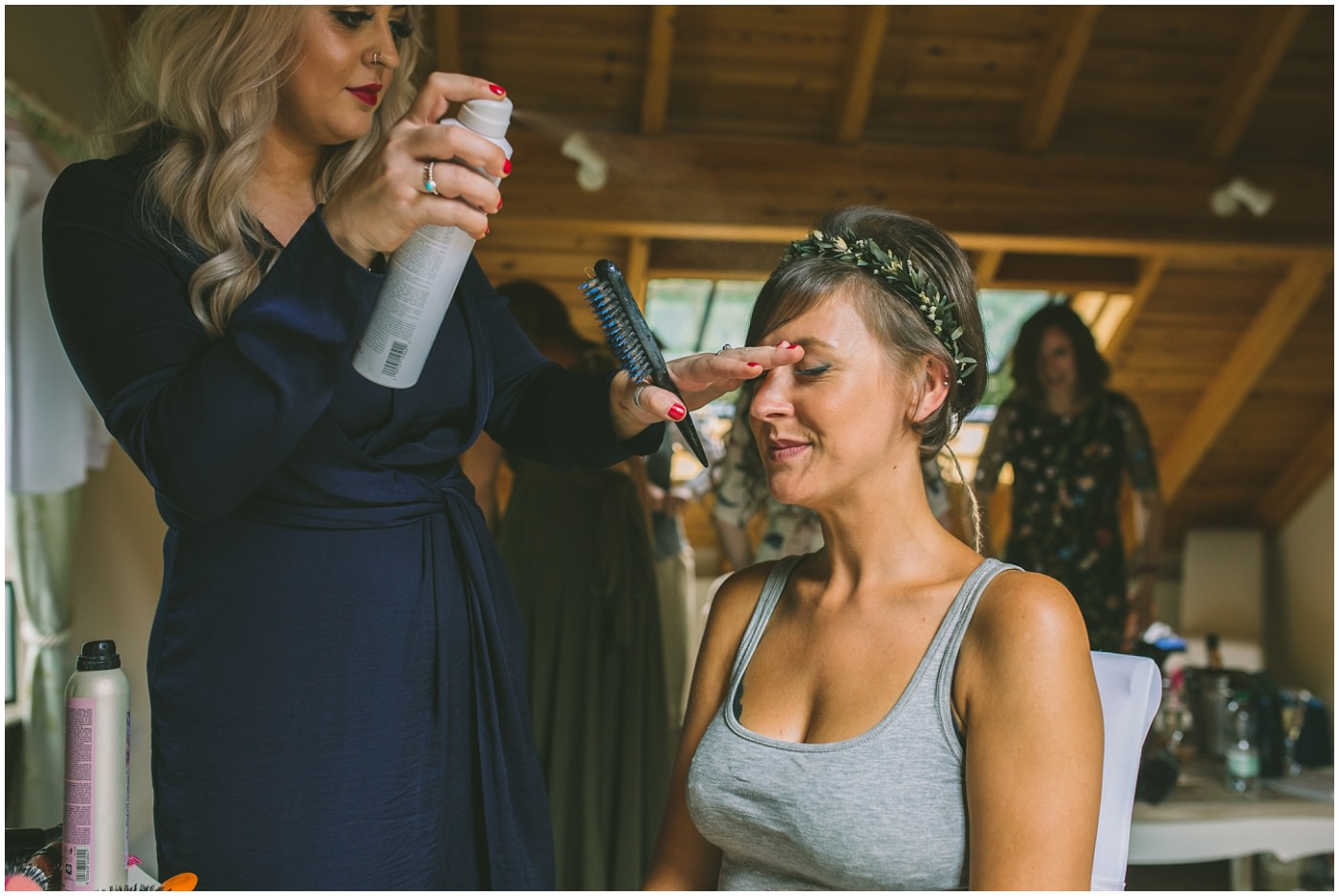 Bride has her hair sprayed by hairdresser
