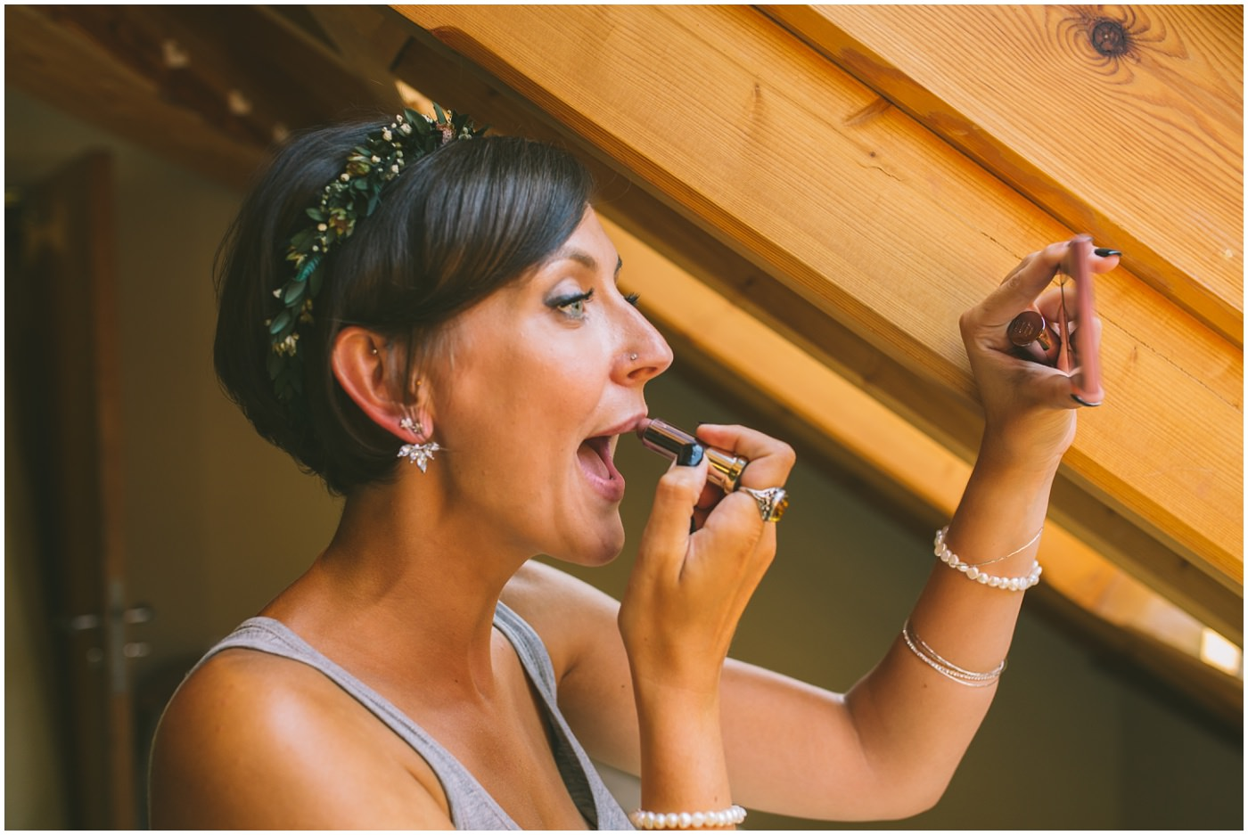 Bride applies lipstick in windowlight