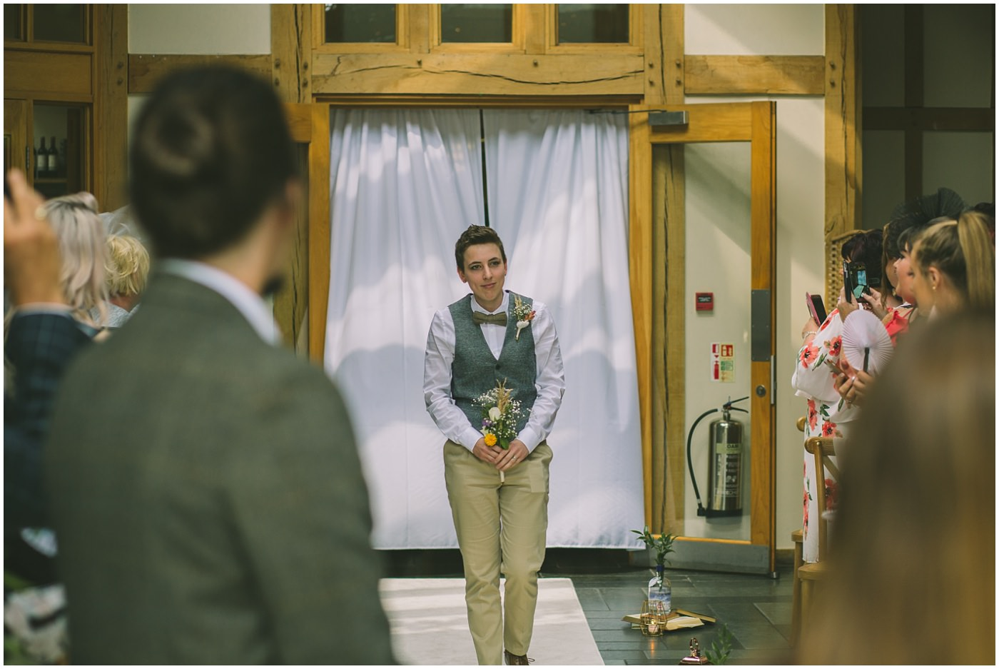 Bridesmaid wearing waistcoat walks down the isle