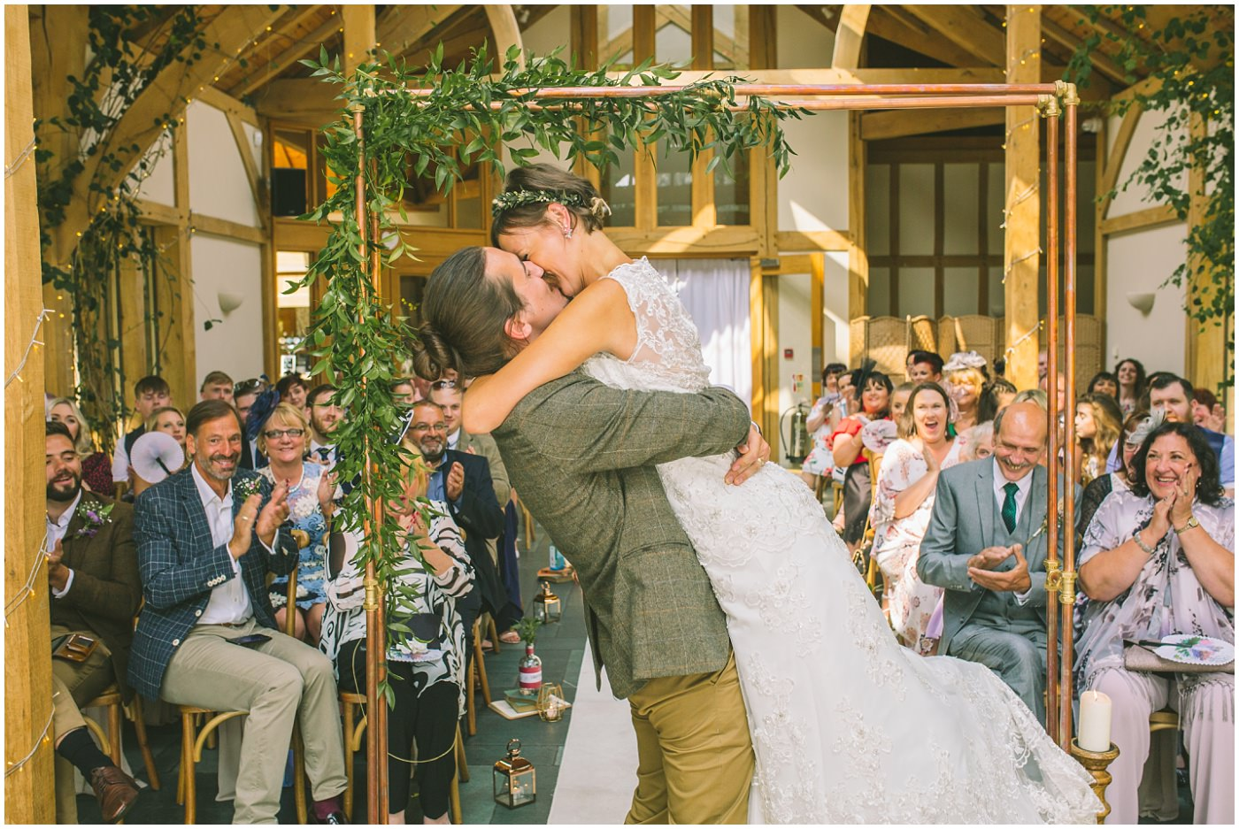 Groom lifts bride as they kiss and a pronounced man and wife