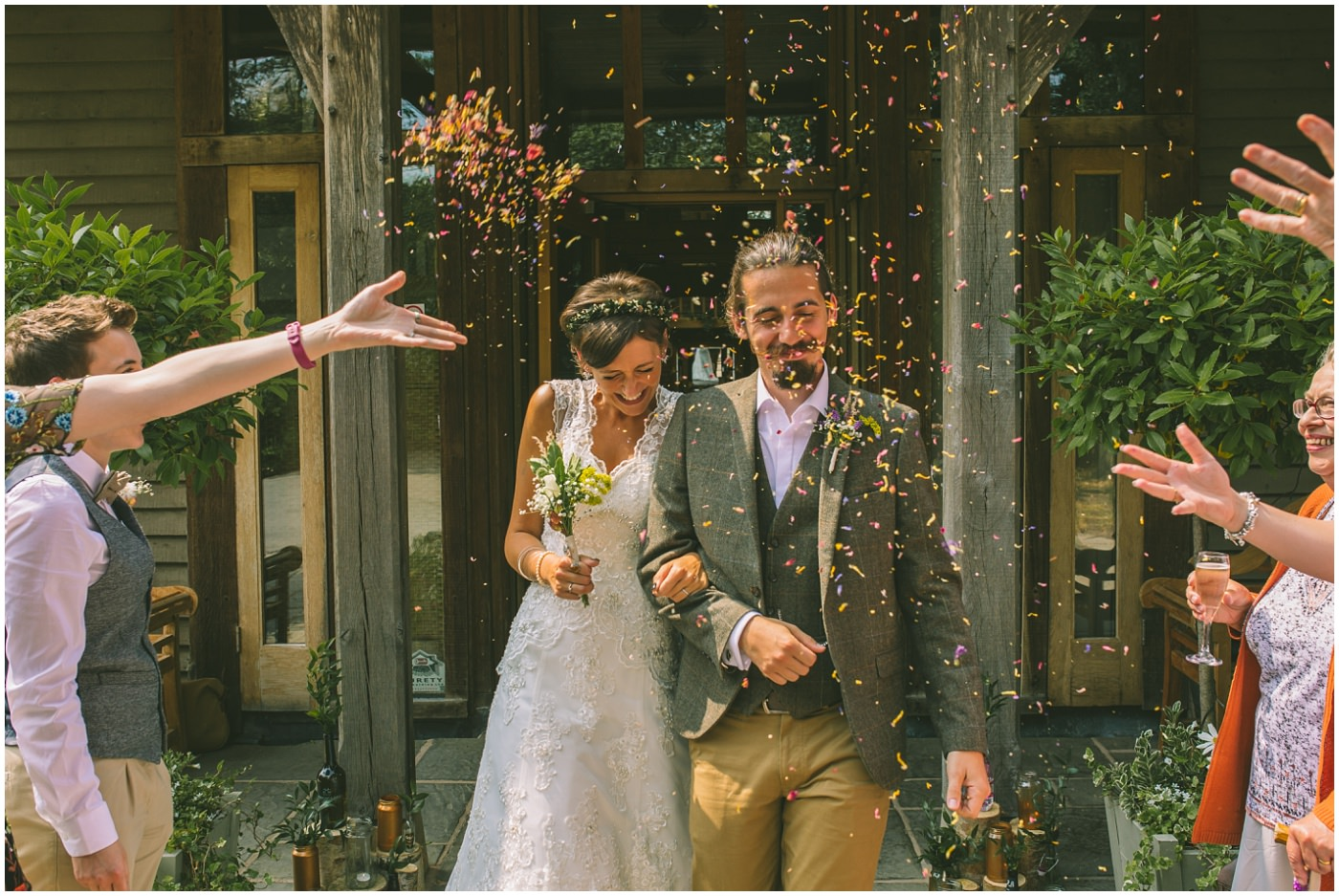 Bride and groom walk arm in arm through confetti
