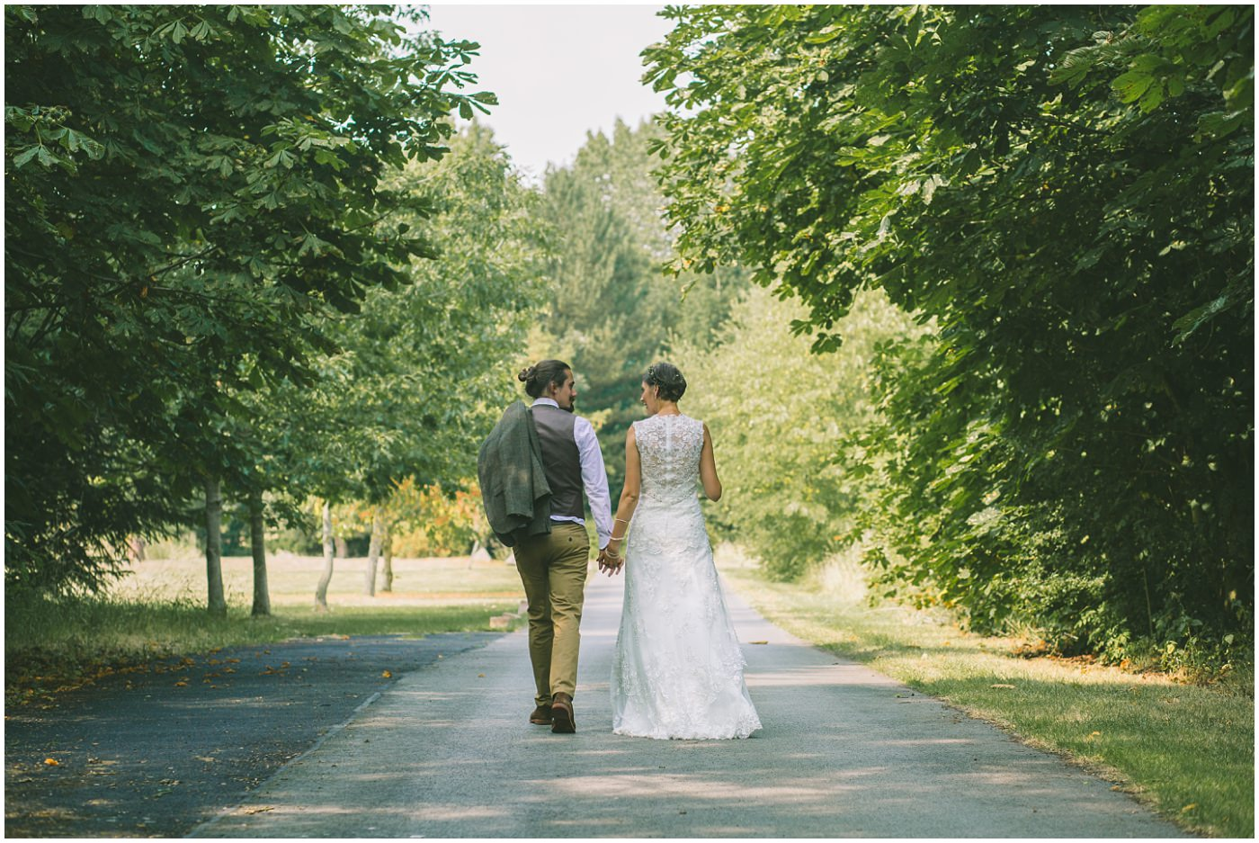 Bride and Groom walk hand in hand down the drive way of the oaktree of peover