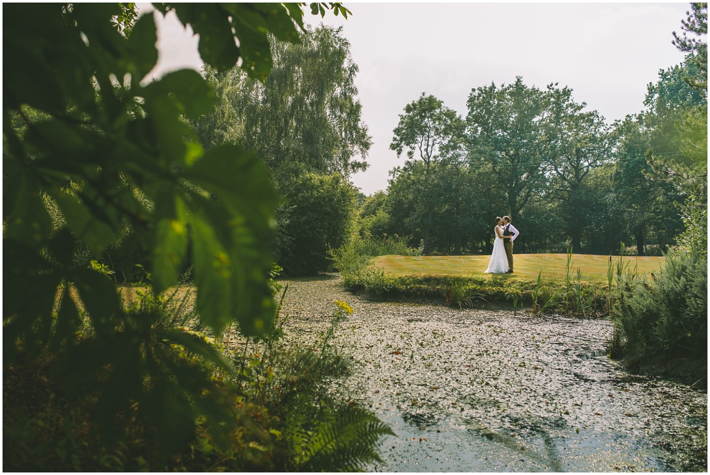 Couples portraits over the lake at the oaktree of peover wedding venue in cheshire