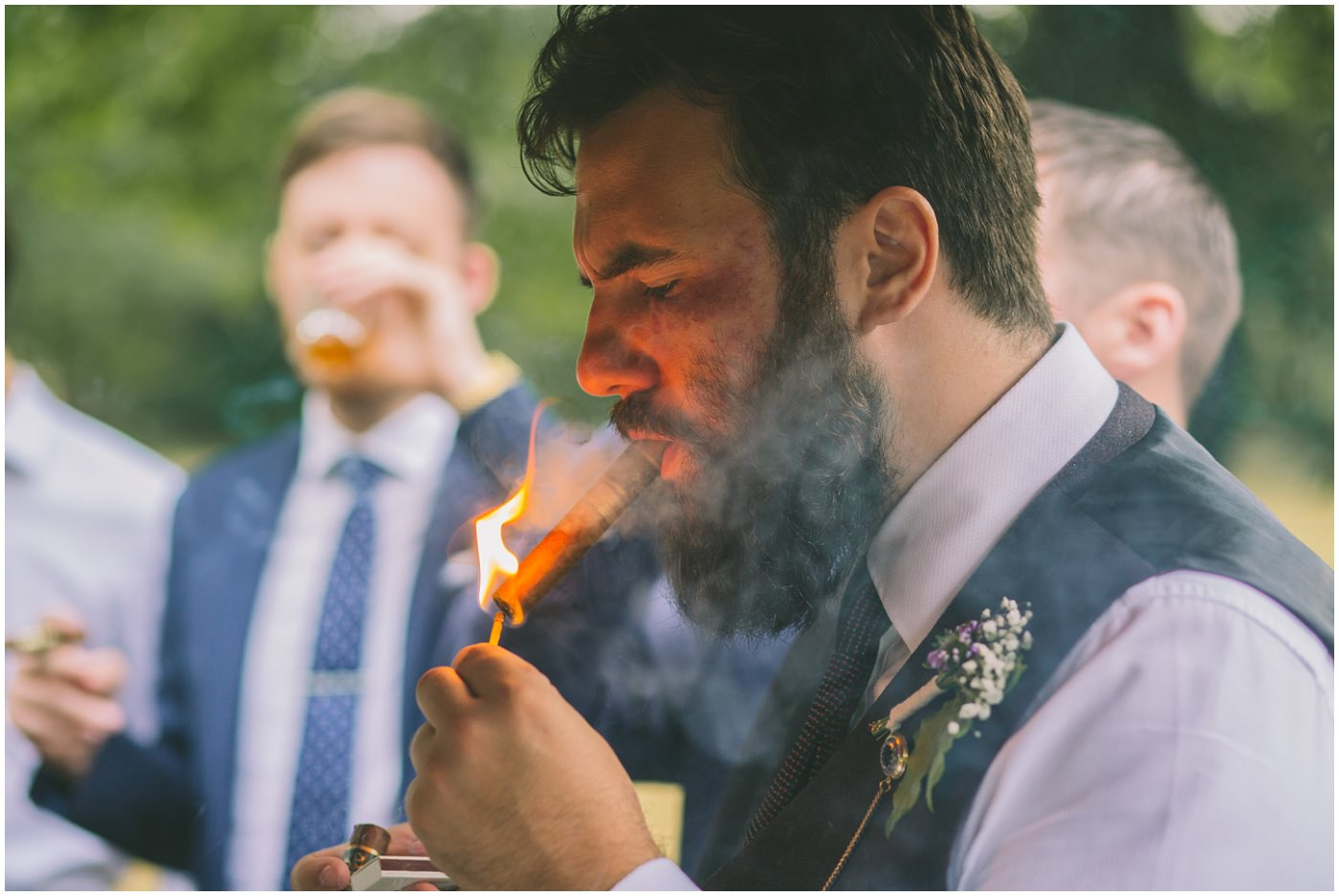 groomsman lights a cigar outside the venue