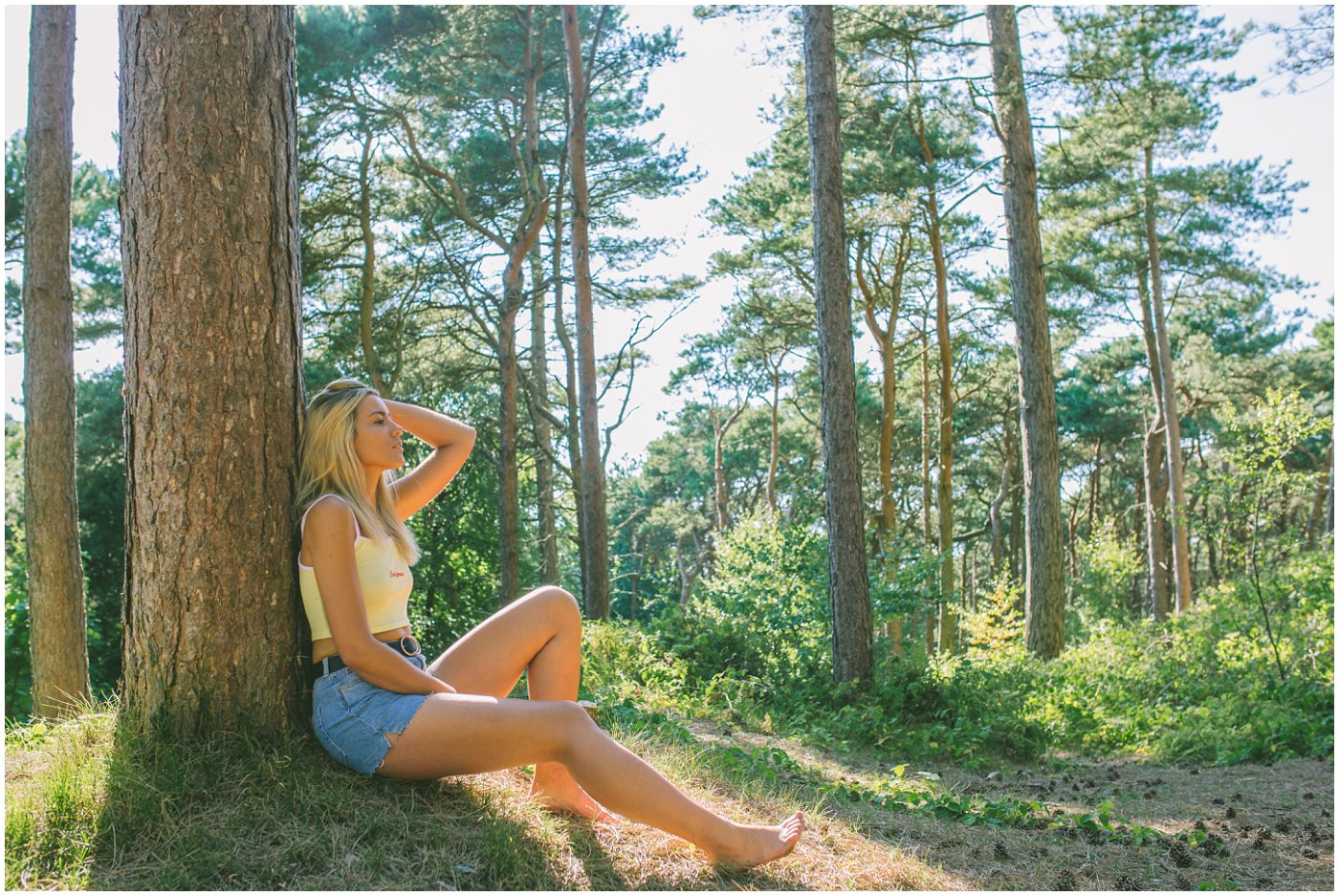 model sits in the sun against a tree at formby