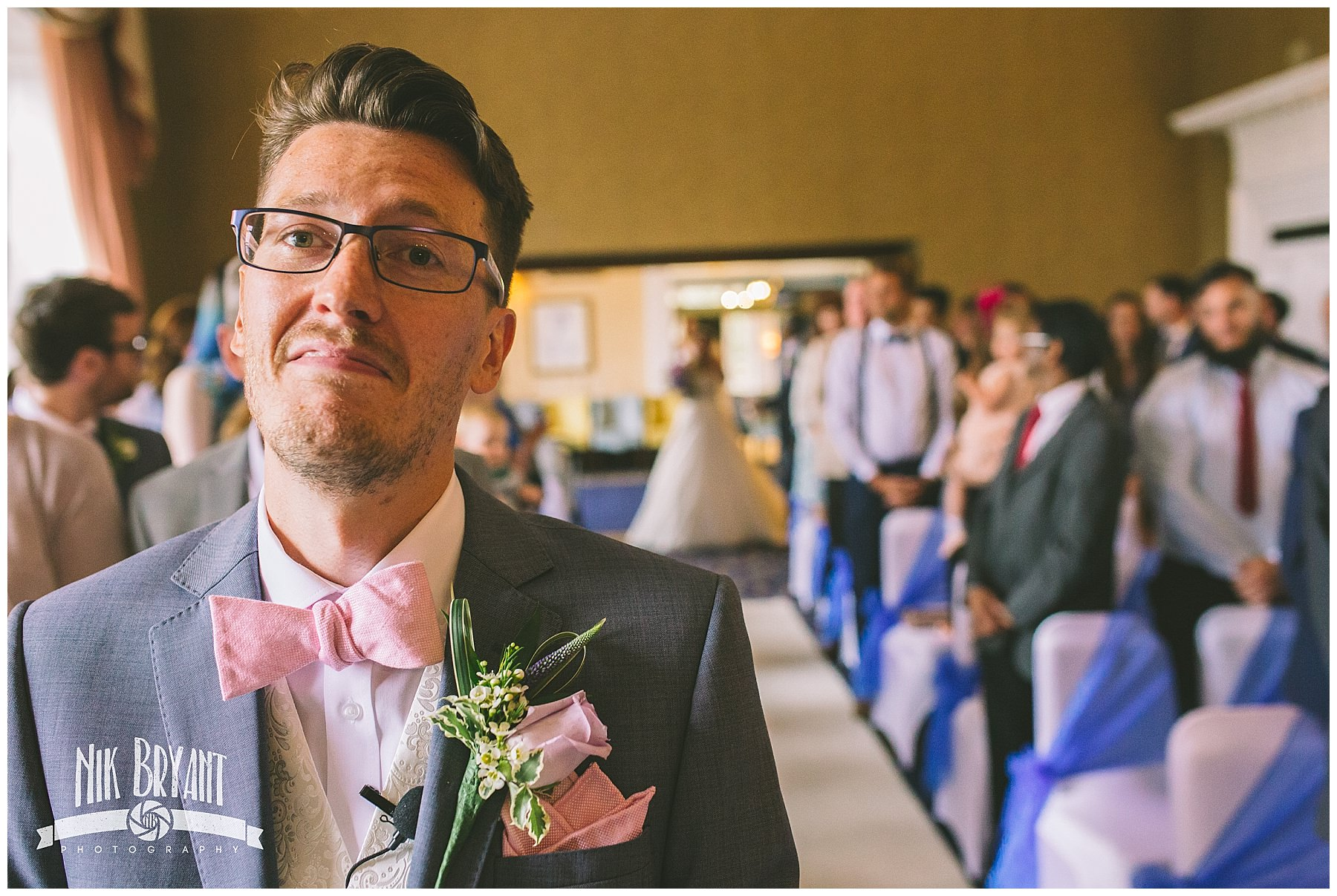 Groom nervously awaits bride to walk down the isle