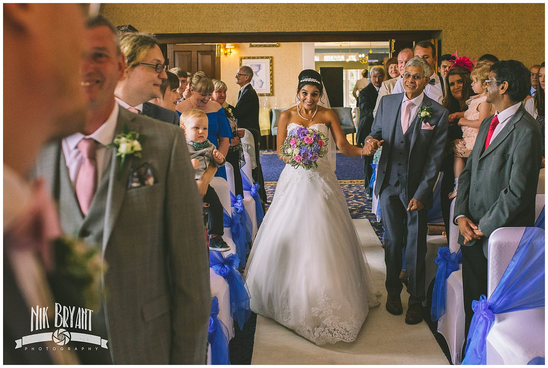 Bride walks down the isle hand in hand with her father