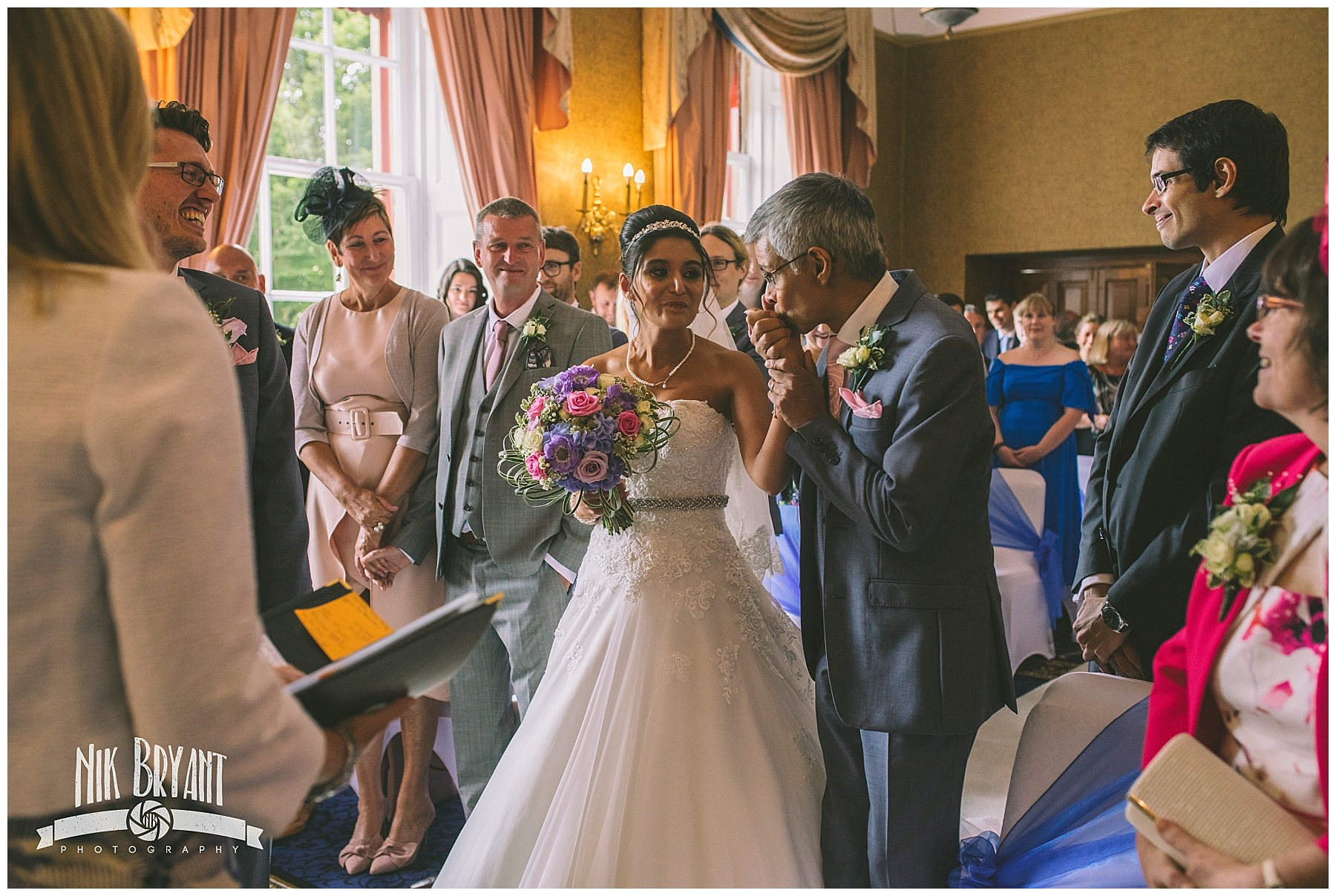 Father kisses his daughters hand as he hands her to the groom at shrigley hall wedding
