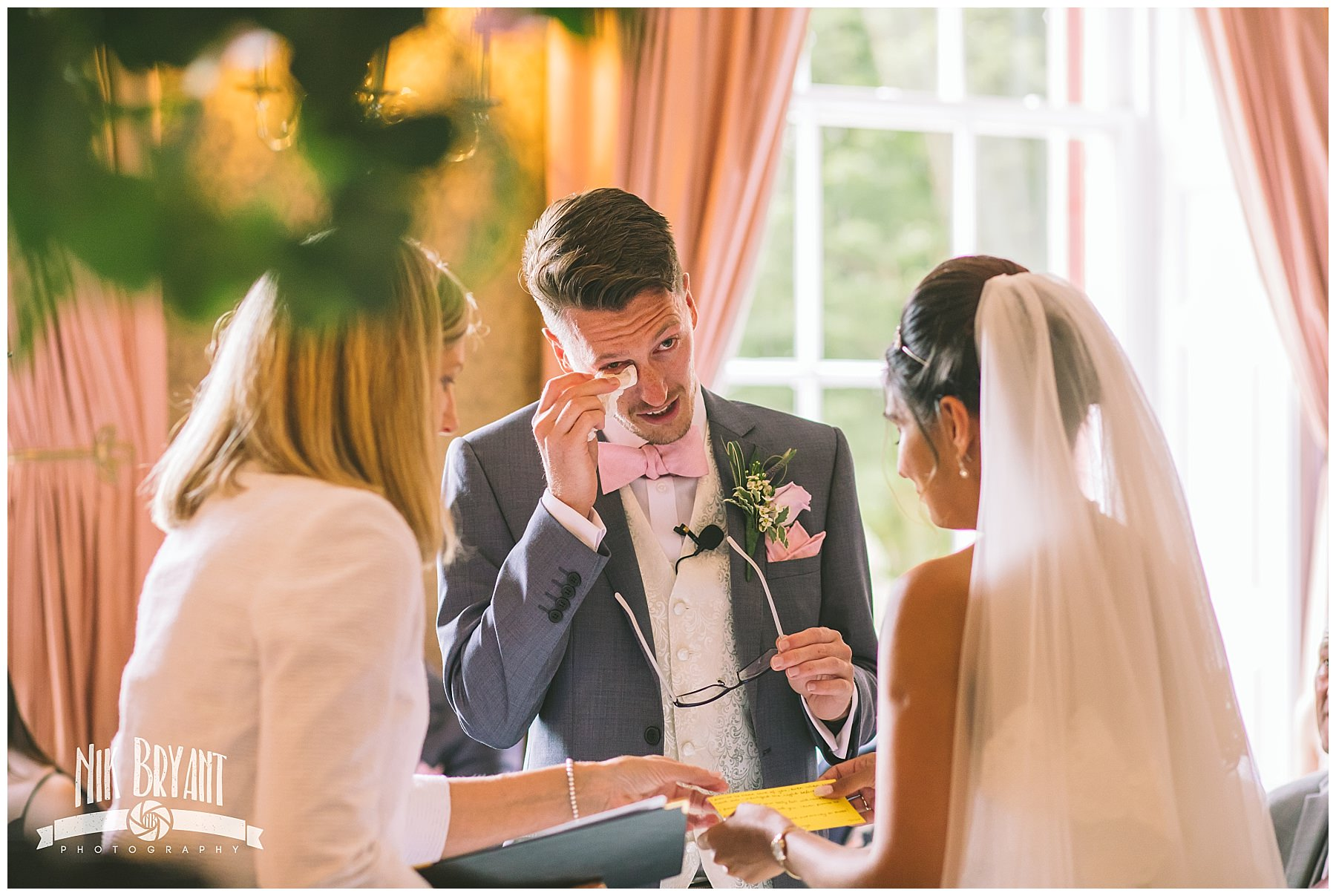 groom wipes a tear from his eye during wedding ceremony