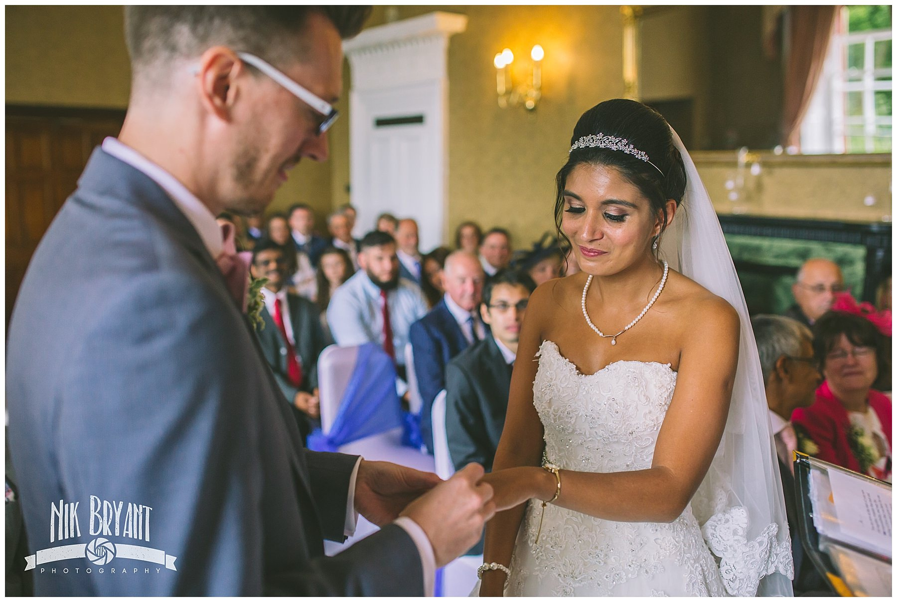Bride and groom exchange rings during wedding ceremony