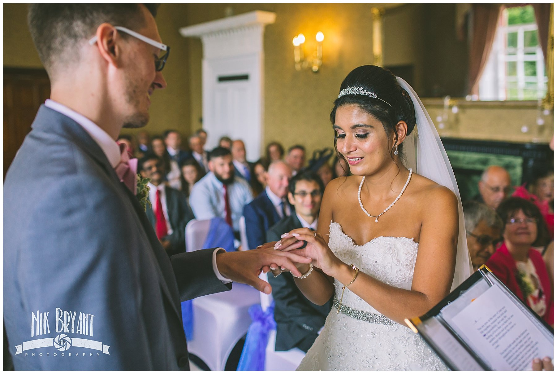 bride gives groom wedding ring during ceremony