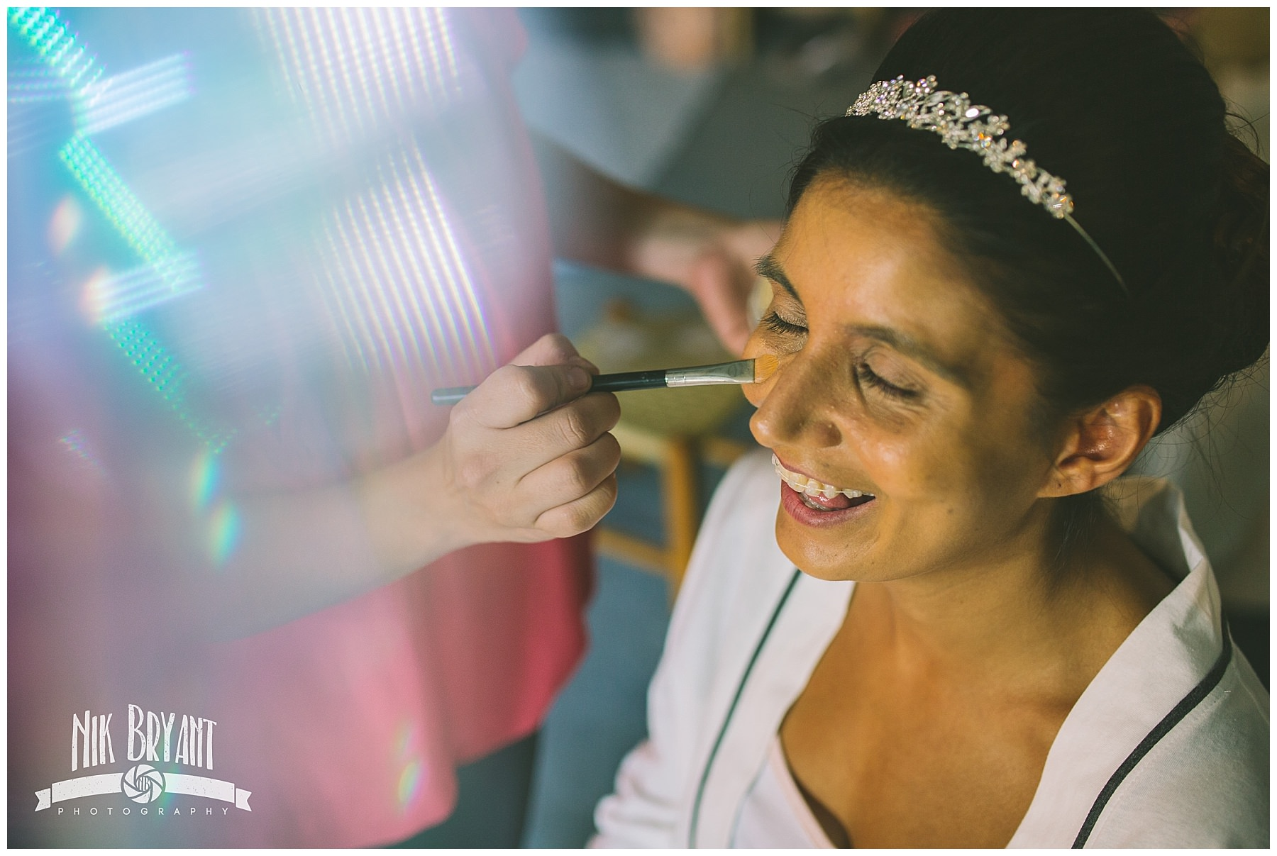 Bride to be laughs as make up is applied