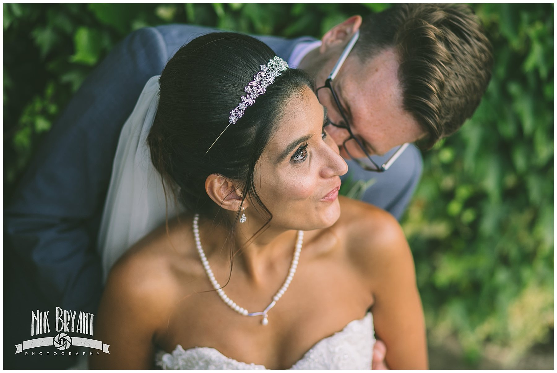 Groom kisses brides cheek during couples portraits