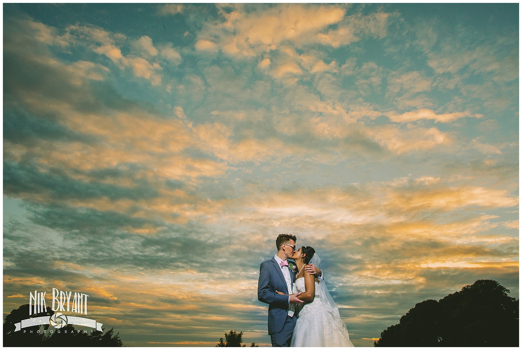 Couple kiss at sunset at Shrigley Hall