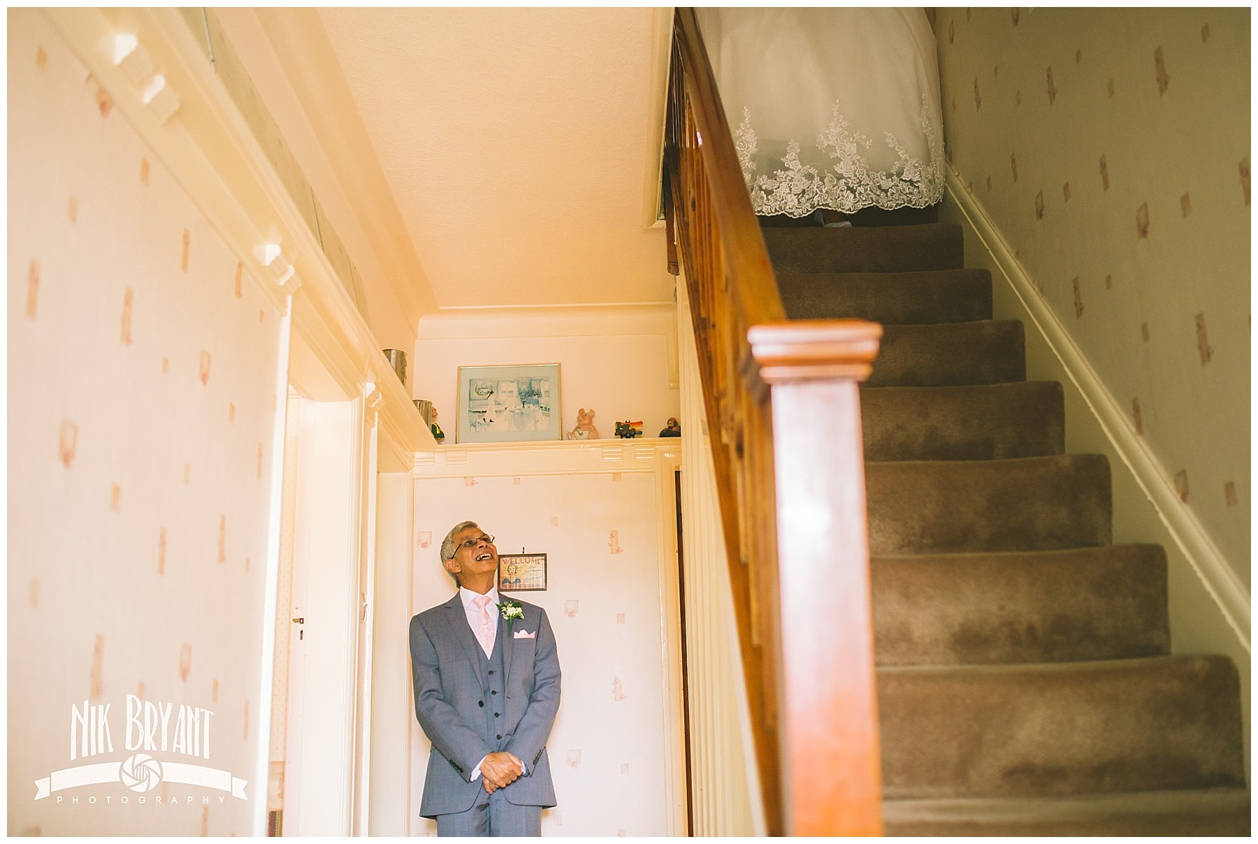 Father of the bride awaits his daughter at the bottom of the stairs
