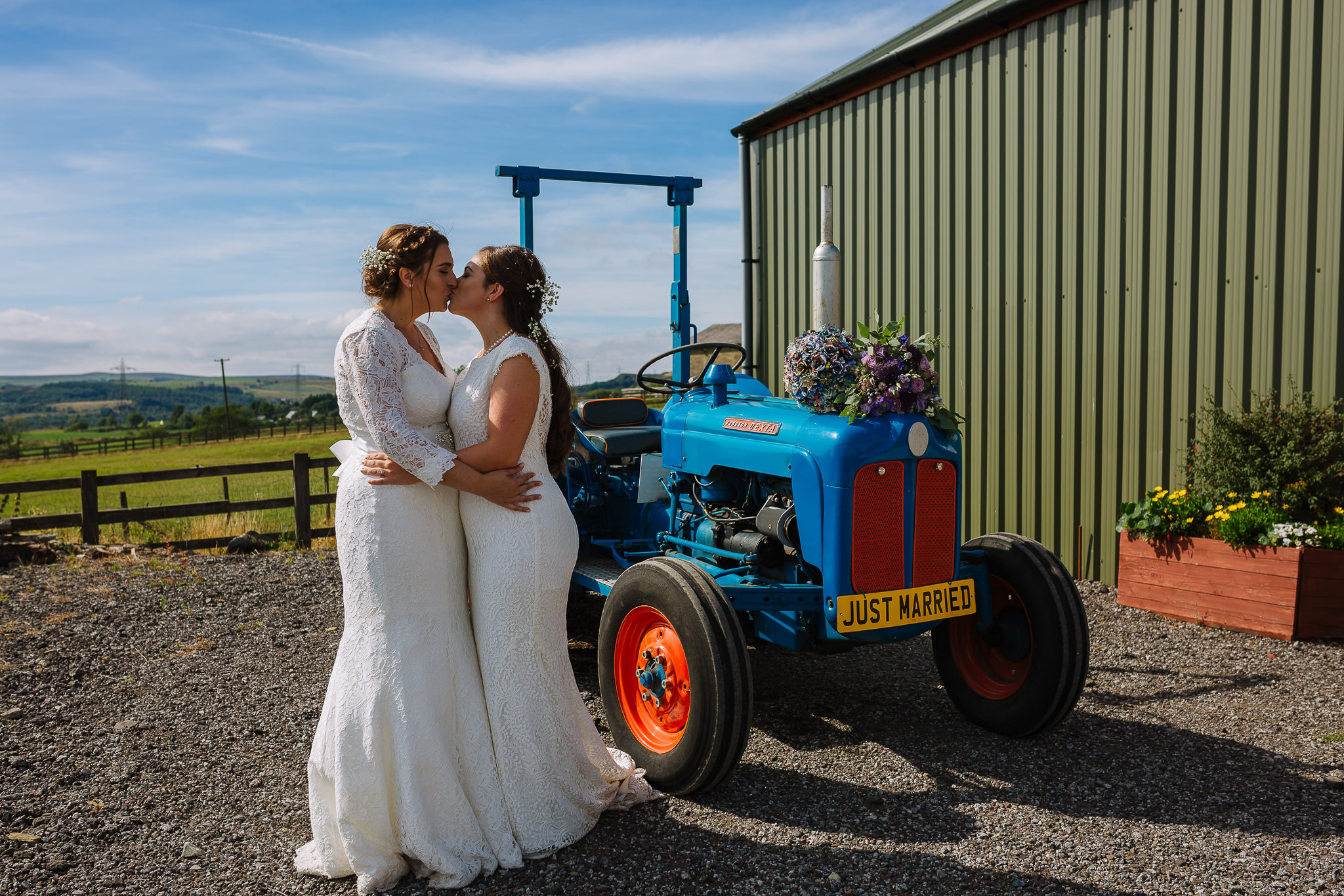 same sex couple kiss in front of the tractor at the wellbeing farm