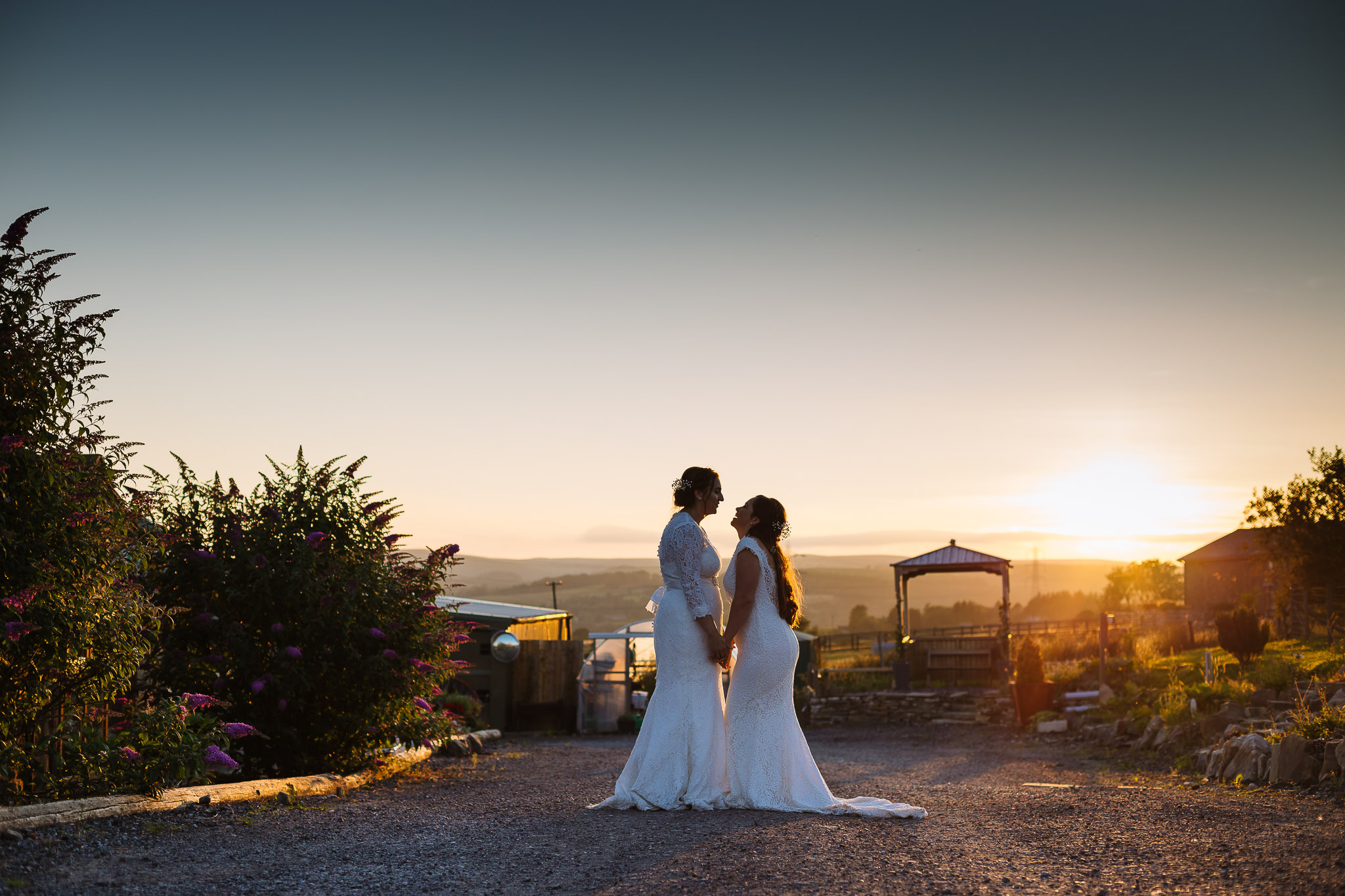 Two brides enjoy sunset at the wellbeing farm same sex wedding