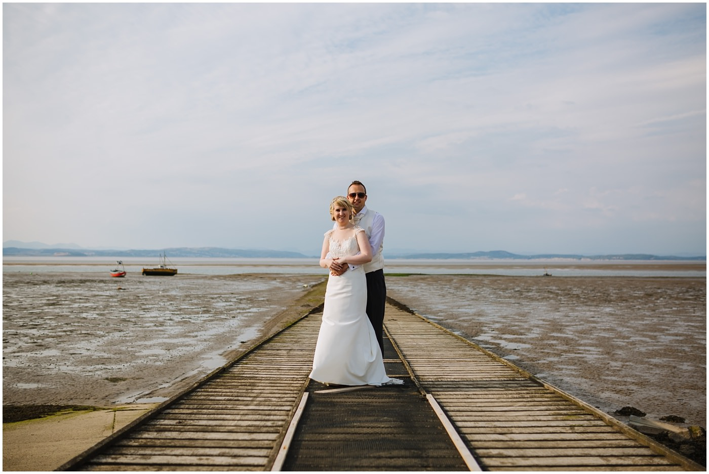 bride and groom embrace on pier at seaside wedding
