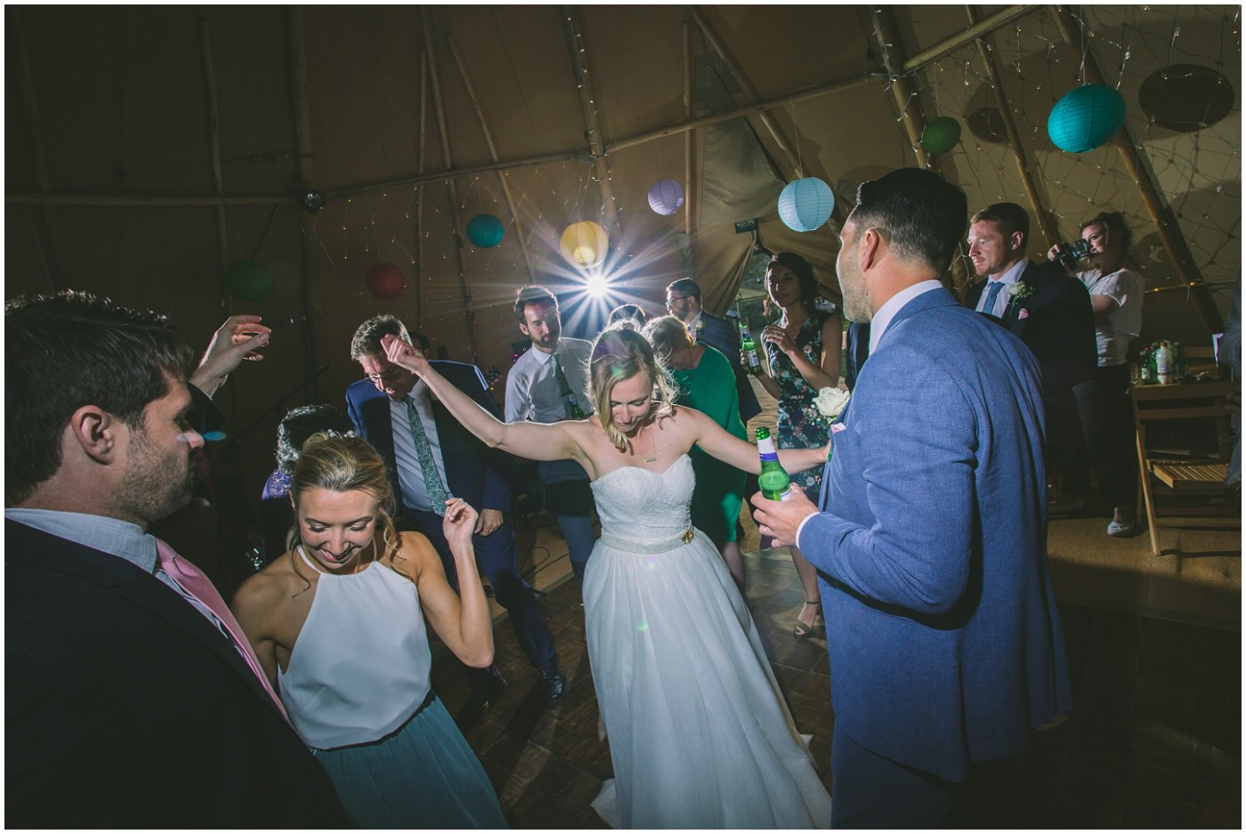 Bride dancing on dance floor at tipi wedding