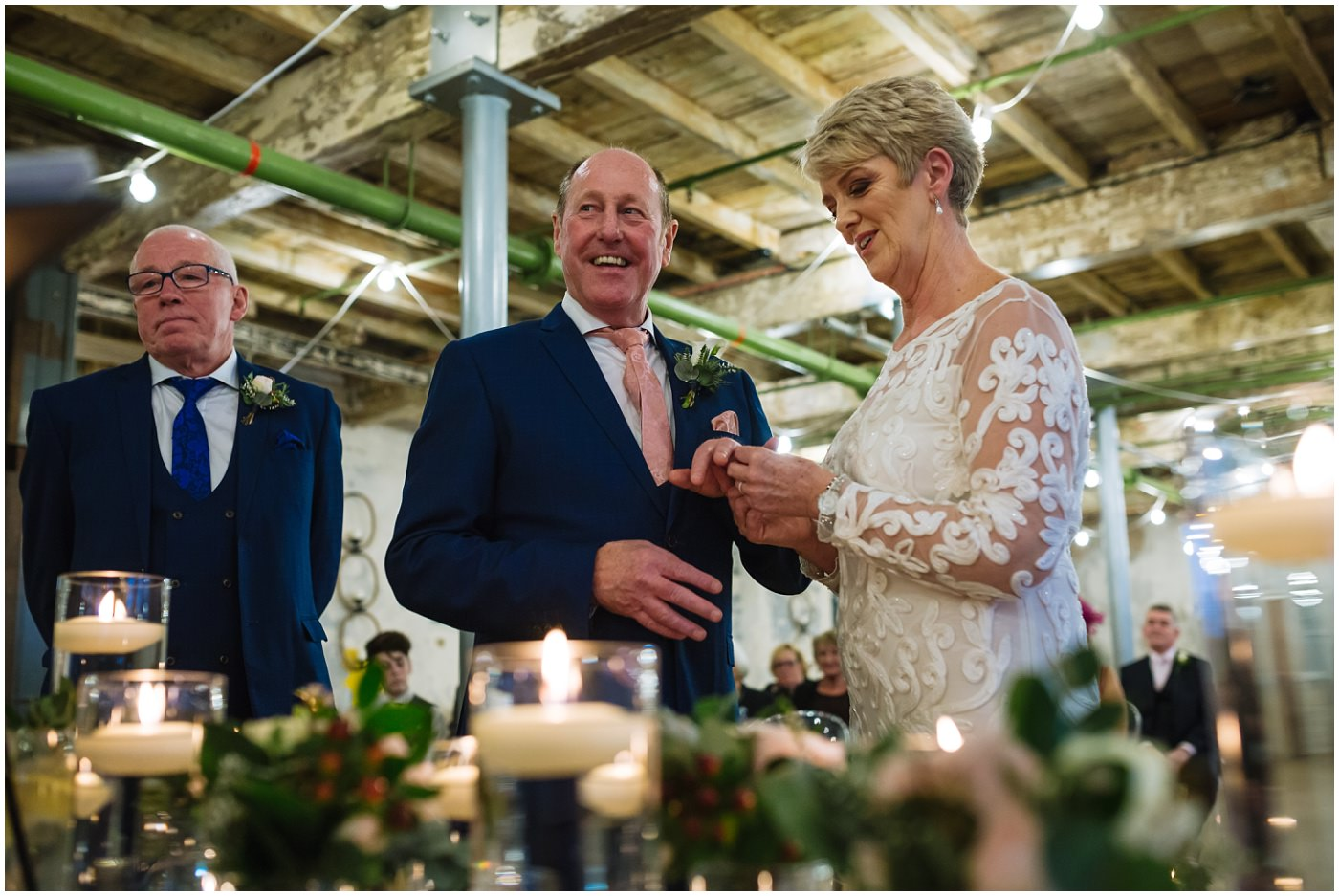 bride and groom smile as they exchange rings during wedding ceremony at holmes mill