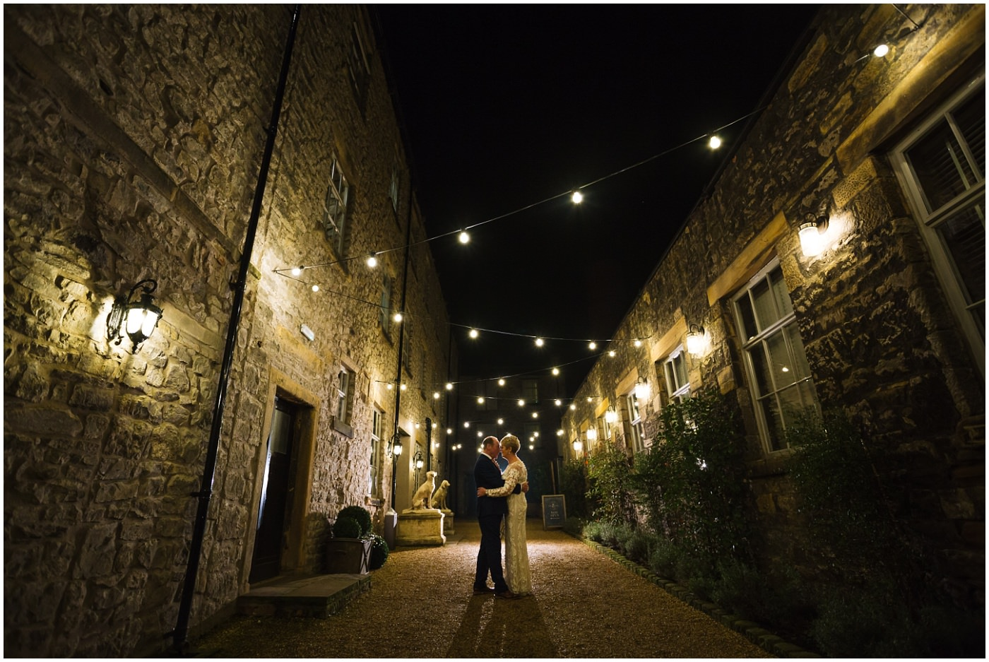 Couple stand under festoon lights at Holmes Mill Wedding