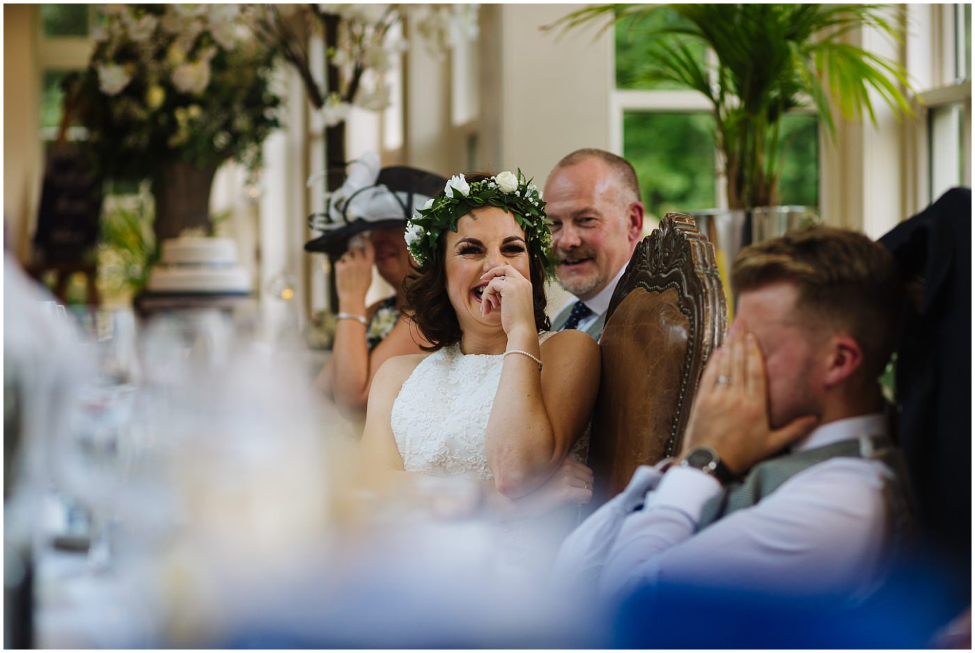 Bride laughs as groom holds head in hands during best mans speech