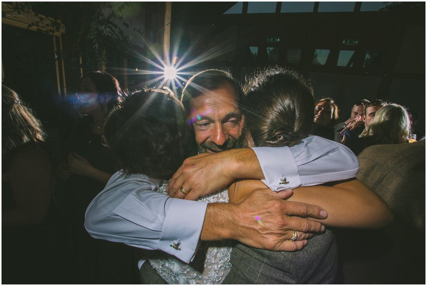 Dad hugs bride and groom on dance floor