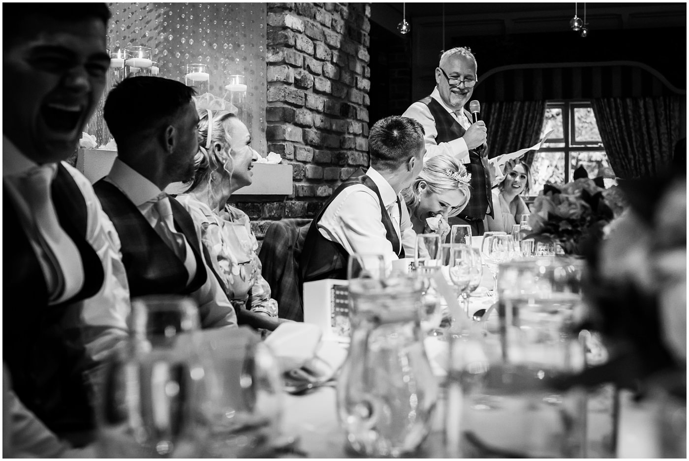 bride and groom laugh at father of the bride speech