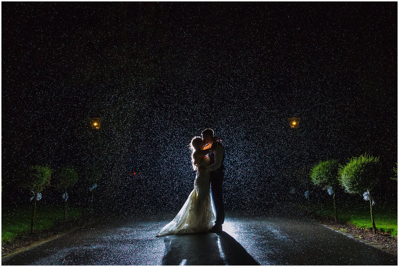Bride and Groom kiss in the rain at Bartle Hall