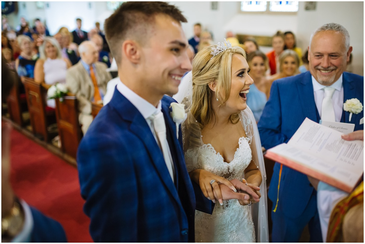 bride laughing during exchange of rings during church service