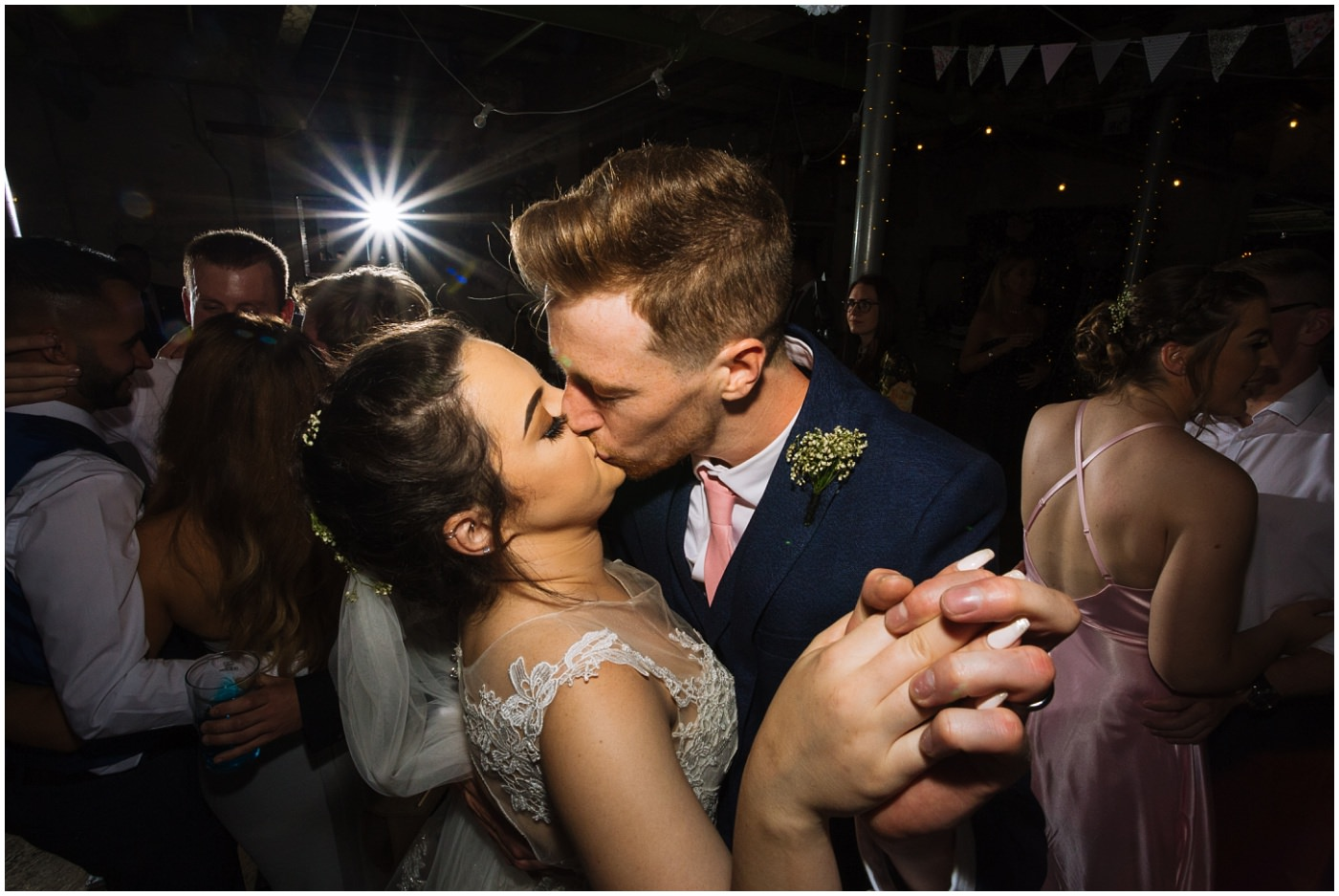 bride and groom kiss on dance floor surrounded by wedding guests