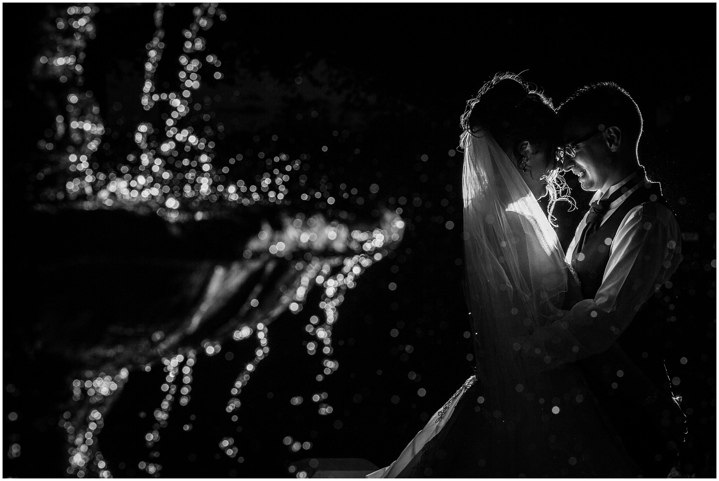 bride and groom in black and white share a moment by a fountain