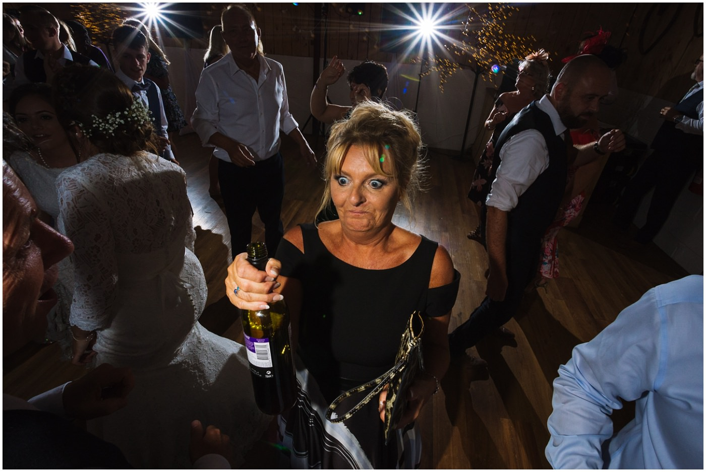 Mother of the bride with a bottle of wine on the dance floor