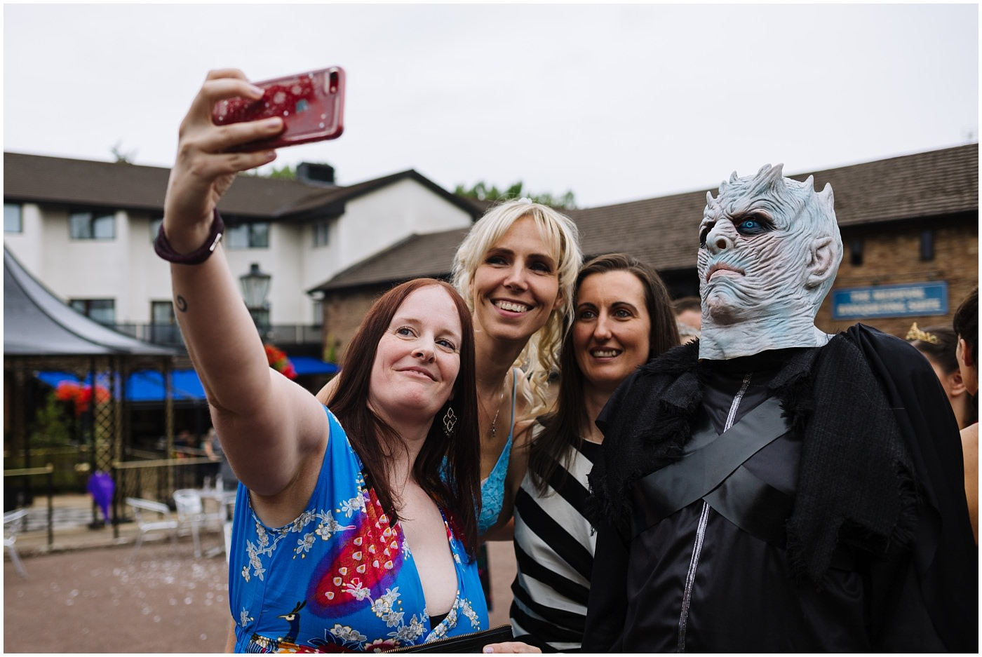 wedding guests take selfie with guest in fancy dress