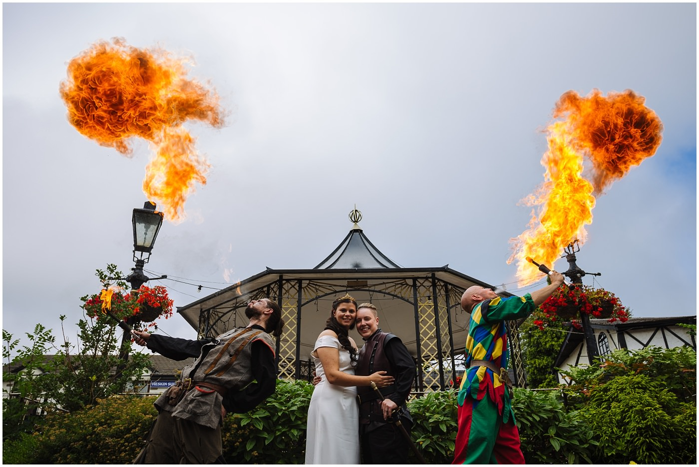 Newly wed couple stand between two fire breathers