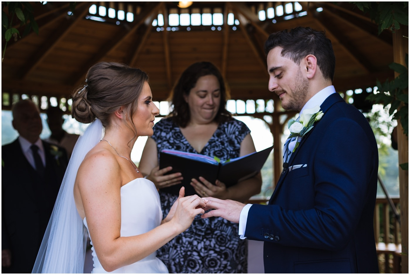 bride and groom exchange rings during outdoor wedding service