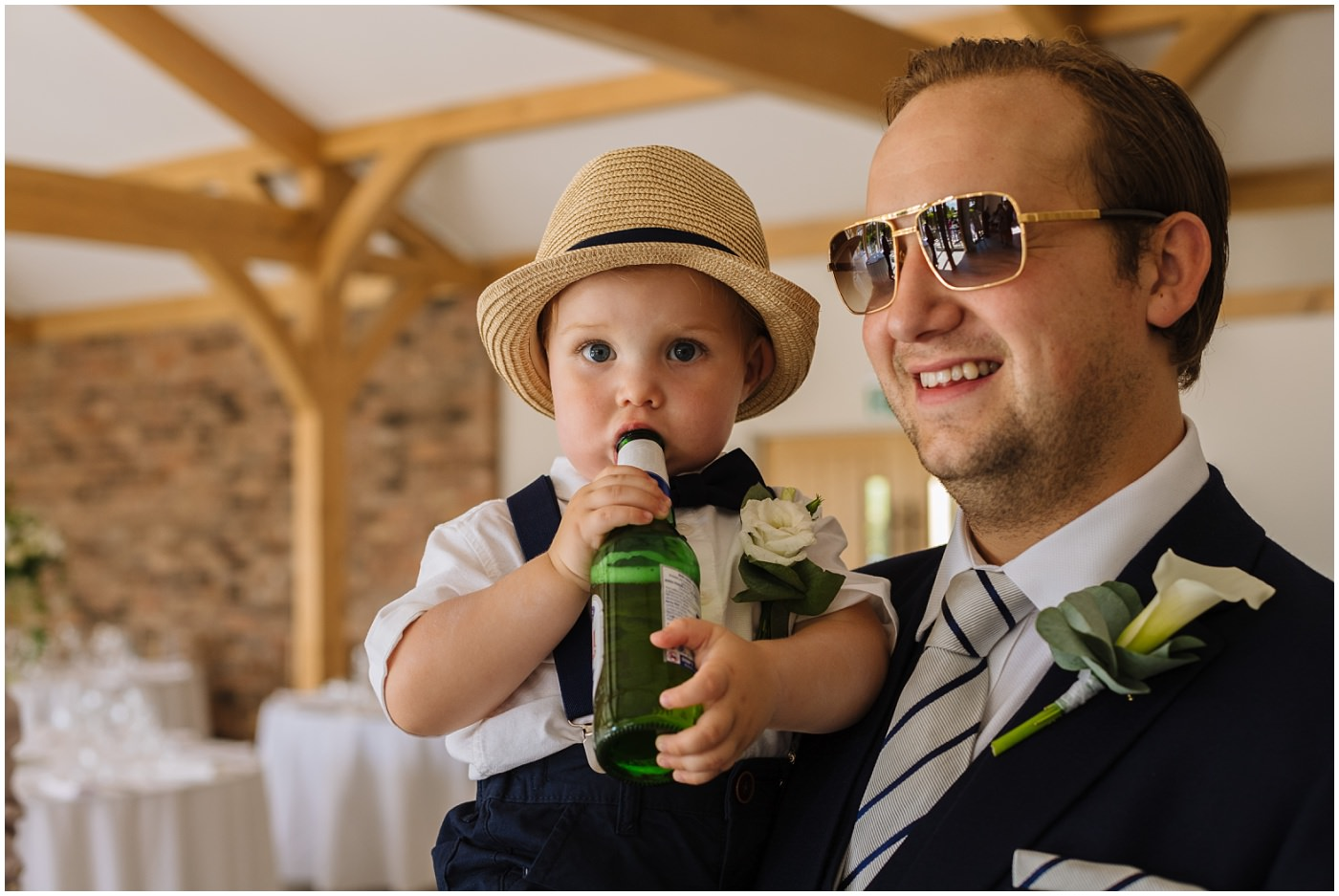 wedding guest holding a child with a beer