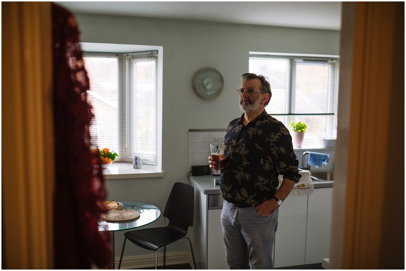 father of the bride stands in kitchen with beer
