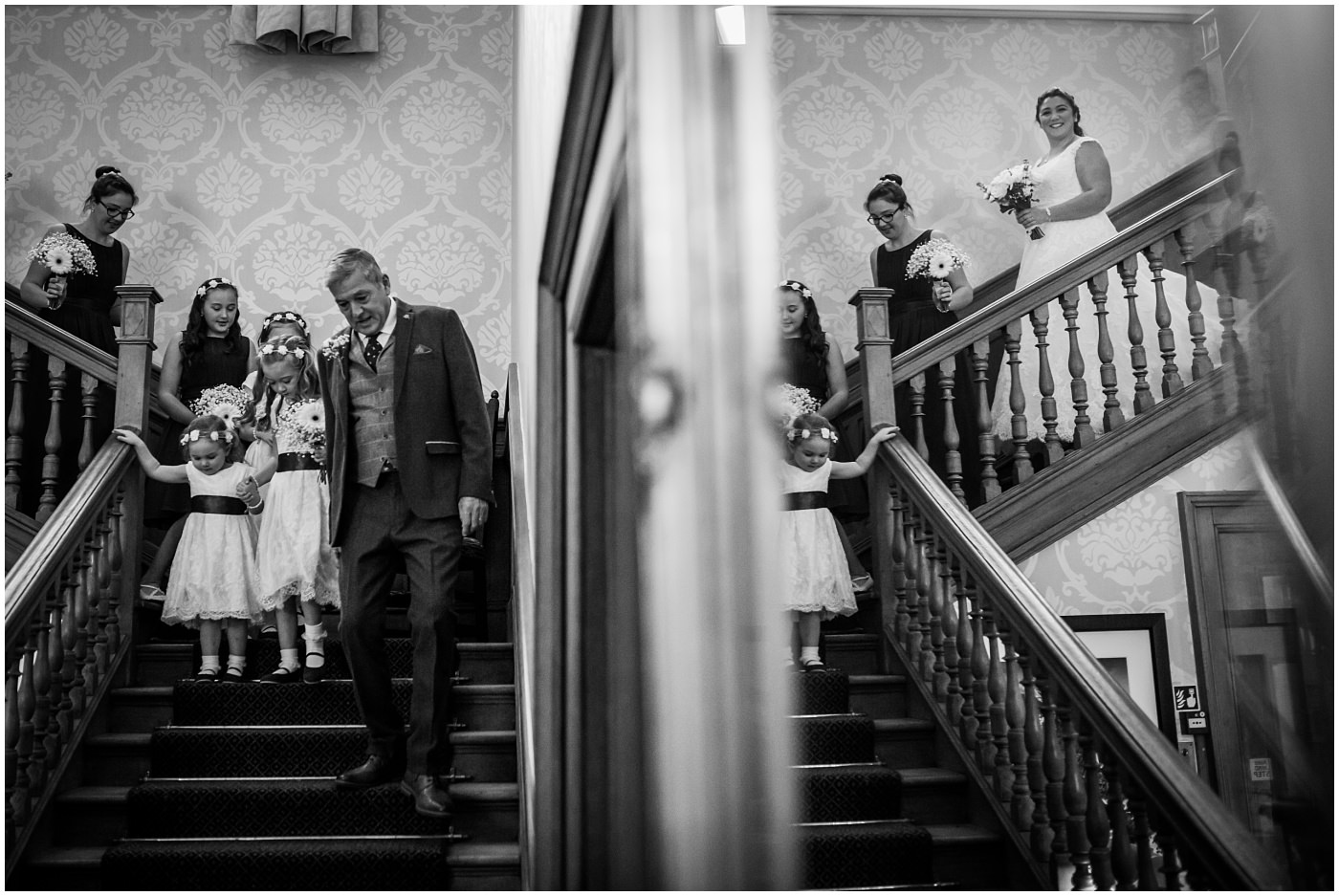 Father of the bride leads bridesmaids and bride downstairs