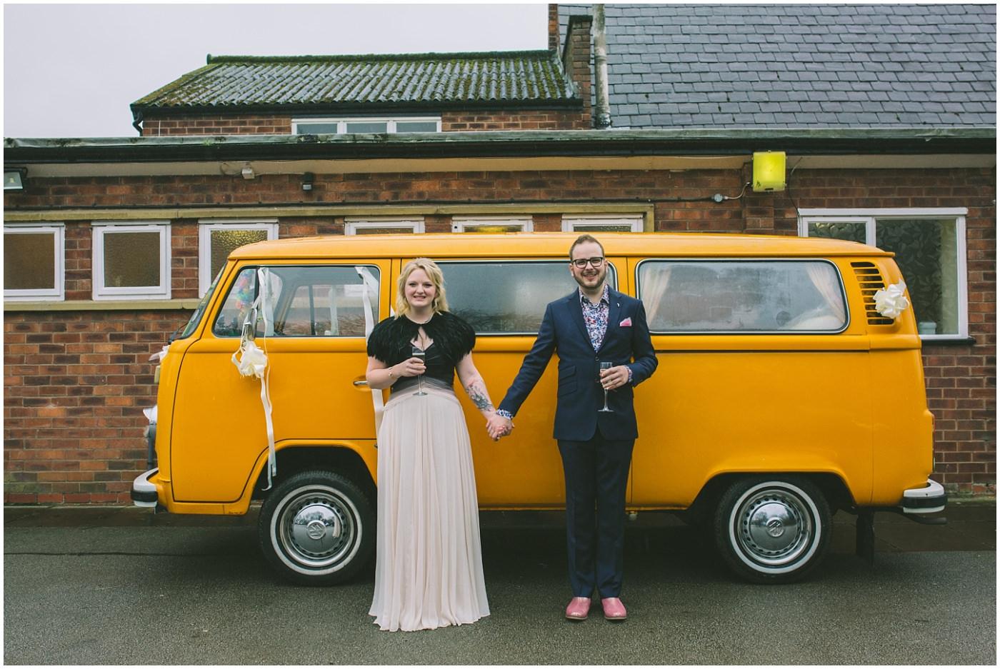 Couple stand holding hands in front of orange camper van