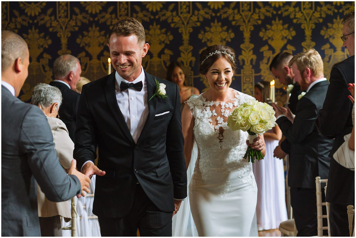 bride and groom leave ceremony room at Soughton Hall and groom shakes hands with a guest