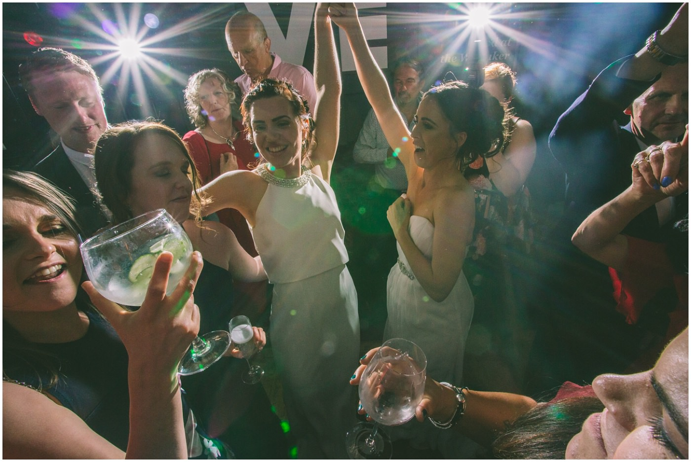 two brides dance surrounded by guests
