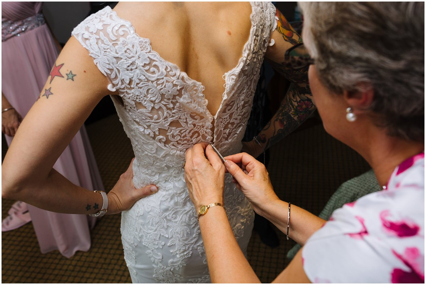 mother of the bride fastens wedding dress
