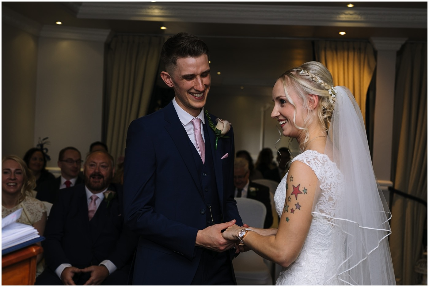 bride and groom smile during wedding ceremony