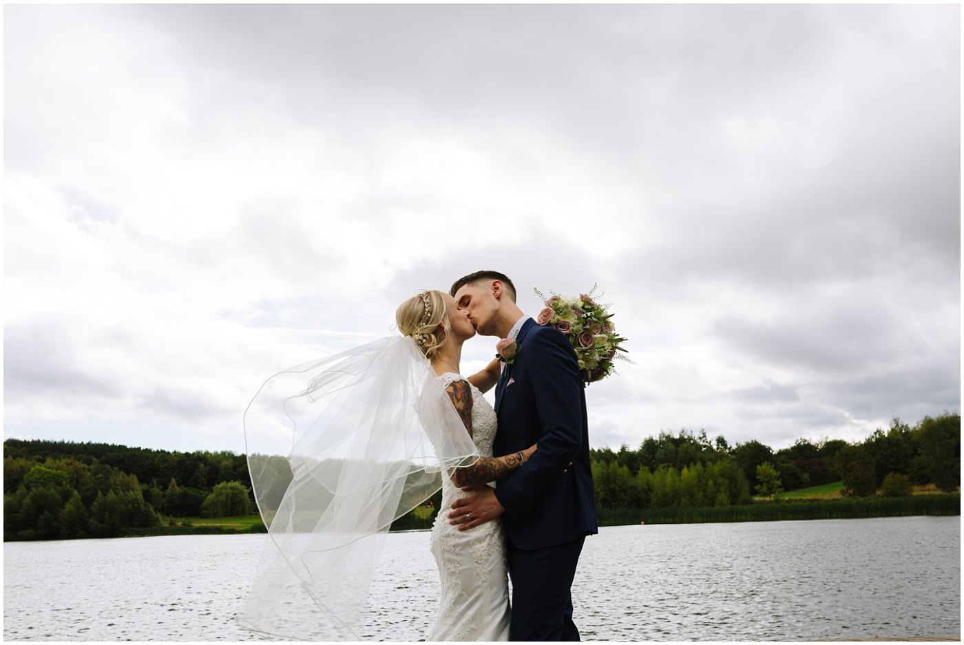 tattooed bride and groom on the lake at walton hall