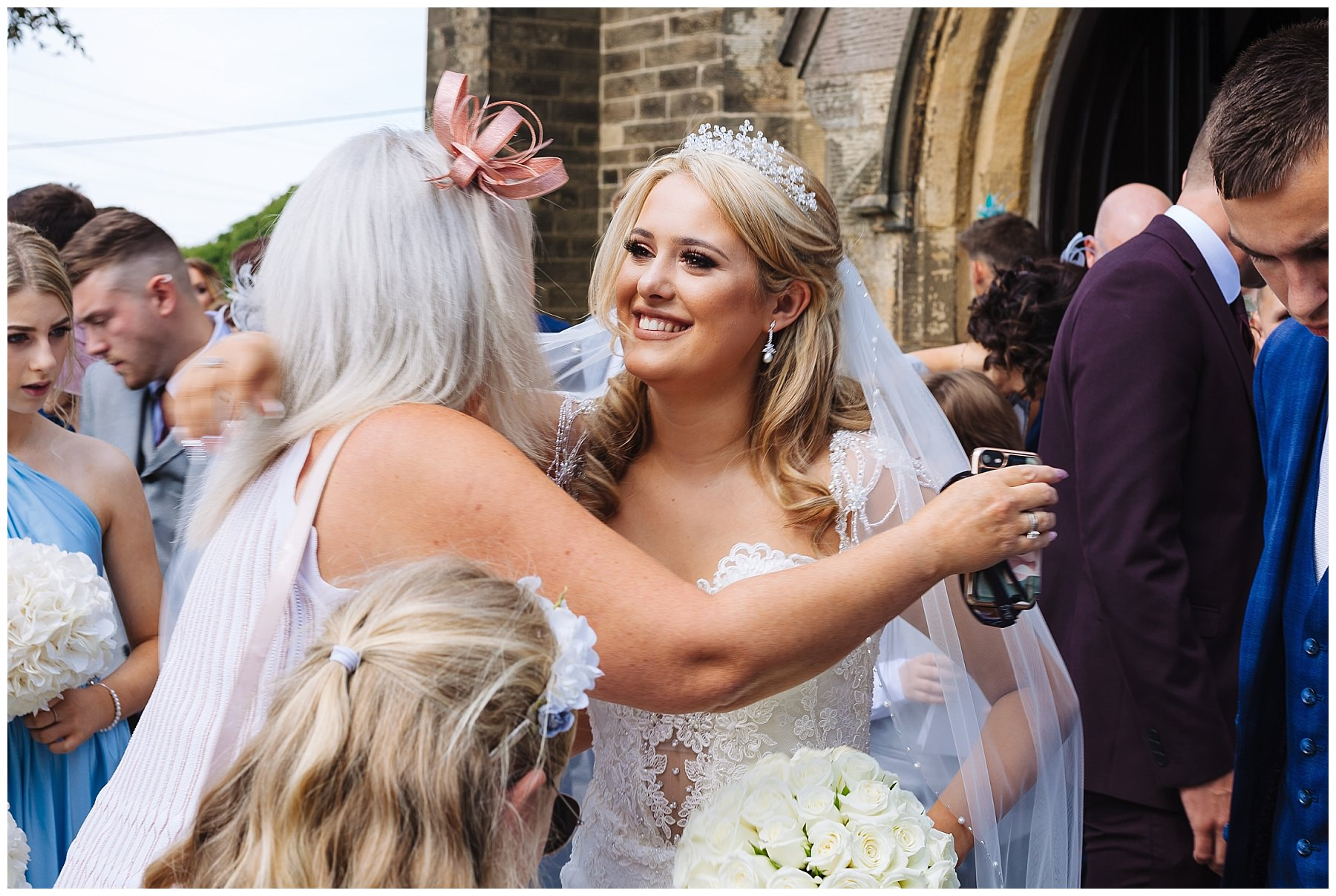 Bride smiles as she hugs guest after Lancashire Church Wedding